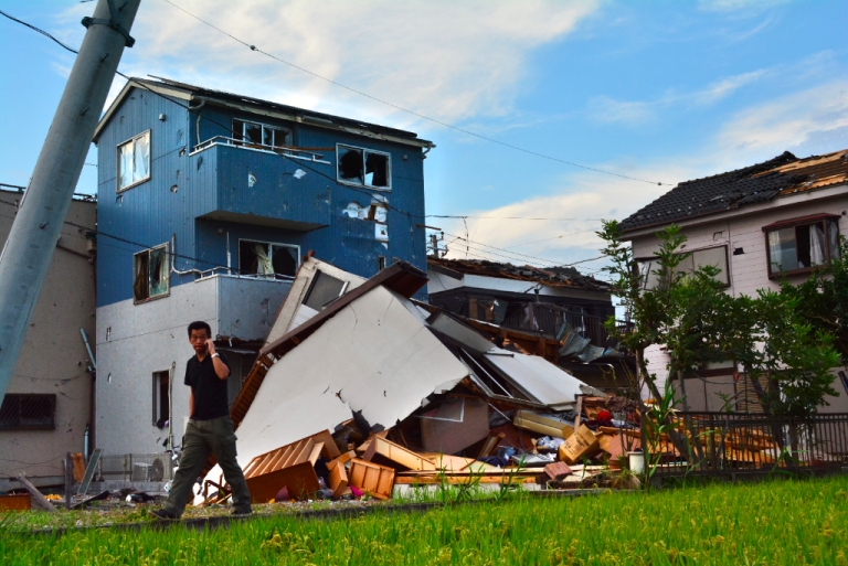 <p>A man walks past damaged houses after a tornado tore through parts of the city of Koshigaya, Saitama prefecture on September 2, 2013. Several dozen people were injured when a tornado ripped through parts of eastern Japan on September 2, tearing off roofs and uprooting buildings</p>