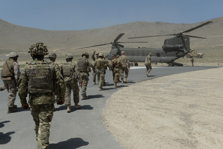 <p>NATO soldiers board a Chinook helicopter after a security handover ceremony at a military academy outside Kabul in 2013.</p>