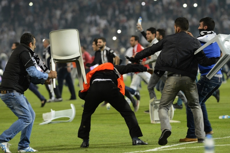 <p>Besiktas football team supporters fight with anti riot police officers during the Turkish super league football match Besiktas vs Galatasaray on Sept. 22, 2013, at the Ataturk stadium in Istanbul.</p>