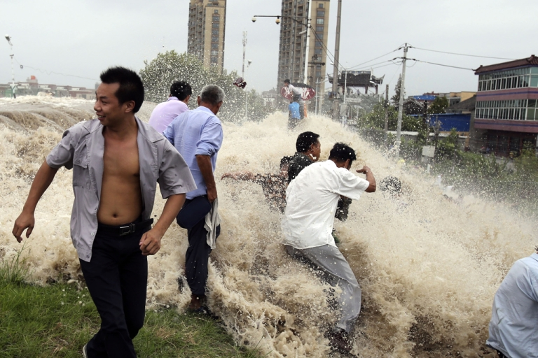 <p>This picture taken on August 22, 2013 shows onlookers being washed away from huge waves from the