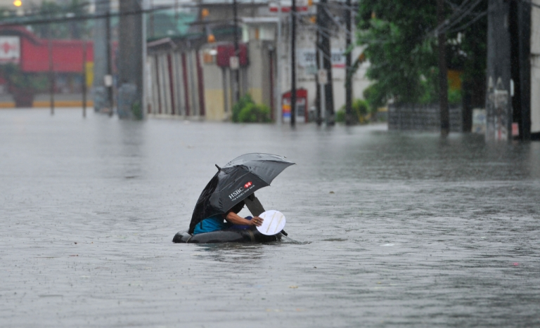 <p>A resident using a innertube as a makeshift raft paddles through chest-deep floodwaters along a street in Manila on September 23, 2013, after torrential rains pounded Luzon island worsened by Typhoon Usagi. Monsoon rains worsened by Typhoon Usagi pounded the Philippines for the third day on September 23, causing floods and landslides that left six people dead and others stranded on rooftops, officials said.</p>