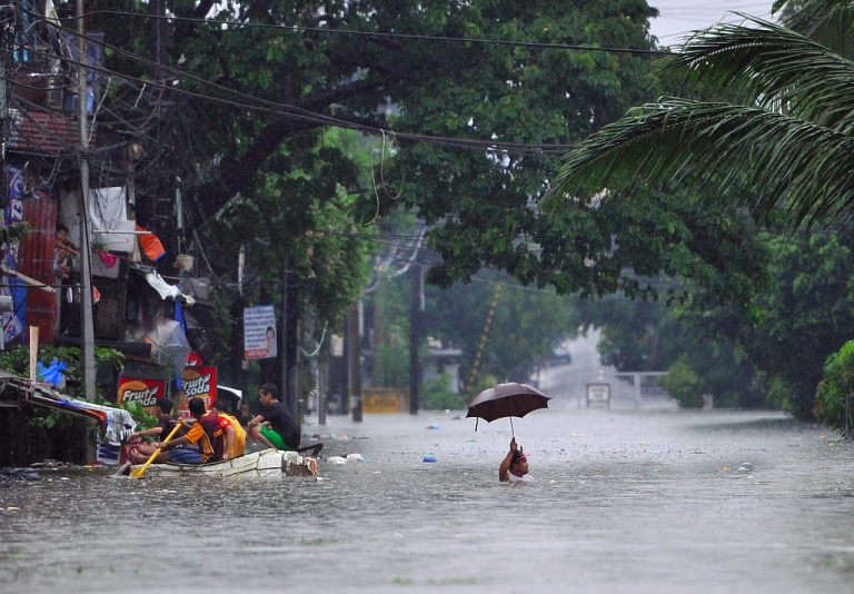 <p>A resident wades through chest-deep floodwaters along a street while his neighbours (L) paddle an improvised life raft in Manila on September 23, 2013, after torrential rains pounded Luzon island worsened by Typhoon Usagi.</p>