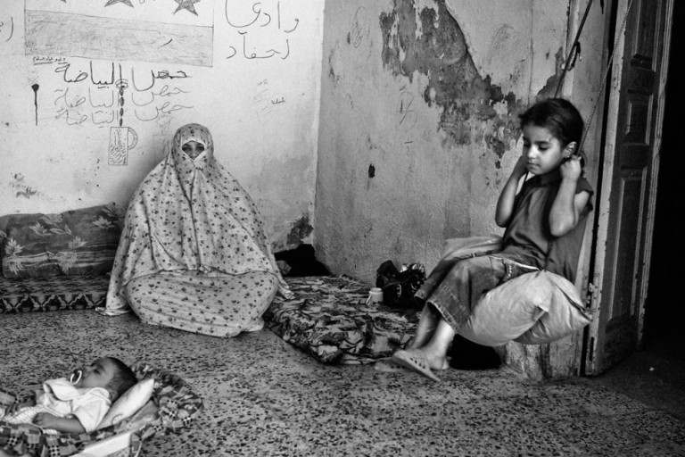 <p>9-year-old Rania * (right), sits on a swing inside her extended family's home in East Amman, an area where many Syrian refugees have rented apartments. Her father and all the men in the family are still in Syria.</p>