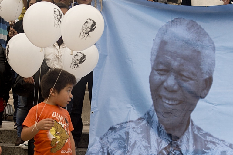<p>A boy accompanying his mother, member of the Conscience and Dignity Foundation, holds balloons with an image of former South African President Nelson Mandela during an event to mark Nelson Mandela International Day at Independence Angel square in Mexico City on July 18, 2013.</p>