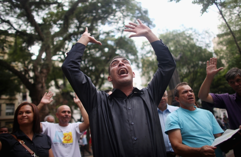 <p>A Protestant (C) preaches to a crowd outside the cathedral of the Roman Catholic Archbishop of Sao Paulo, Cardinal Odilo Pedro Scherer, on March 11, 2013 in Sao Paulo, Brazil. Brazil has more Catholics than any other country in the world but a boom of evangelical Protestantism in Brazil is steadily eroding the dominance of the Catholic church in Brazil.</p>