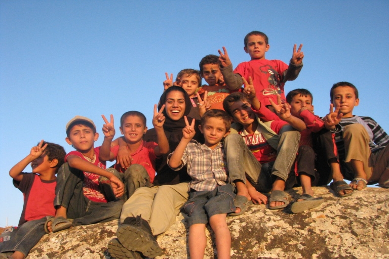 <p>Puneh Alai'i on a rock with all the village boys giving a peace sign during her most recent trip inside Syria in September 2013.</p>