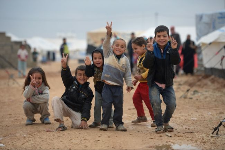 <p>Children pose for a picture as Syrian refugees go about their daily business in the Za'atari refugee camp on Feb. 1, 2013 in Jordan.</p>