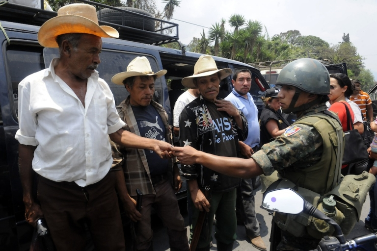 <p>A Guatemalan soldier frisks a driver at a checkpoint on a road in Mataquescuintla municipality, Jalapa departament, 125 km southeast of Guatemala City on May 2, 2013. President Otto Perez Molina ordered a state of siege for 30 days in four municipalities in southeastern Guatemala just days after security forces clashed with opponents of a Canadian-owned gold and silver mine project who had taken 23 officers hostage.</p>