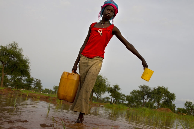 <p>A woman carries heavy jugs of water through a muddy pond where she filled the plastic containers July 17, 2012 in Jamam refugee camp, South Sudan.</p>