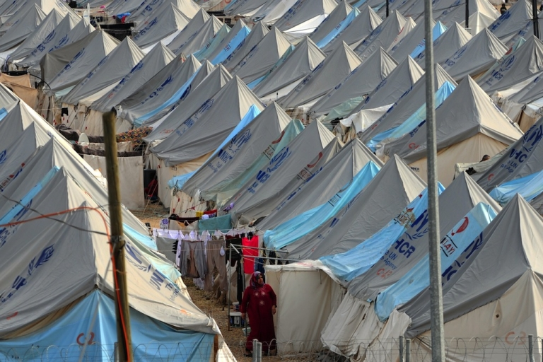 <p>A Syrian refugee woman walks among tents at Karkamis' refugee camp on January 16, 2014 near the town of Gaziantep, south of Turkey.</p>