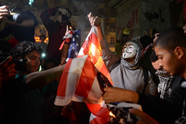 <p>Egyptian men, one wearing a mask of Guy Fawkes, set fire to a US flag as protesters and supporters of the Muslim Brotherhood take part in a march against the military in the capital Cairo on January 22, 2014.</p>