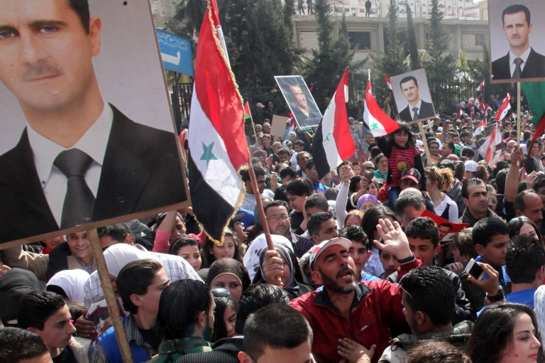 <p>Syrians holding portraits of President Bashar al-Assad and waving national flags take part in a rally to show their support to the government on February 22 in Damascus.</p>
