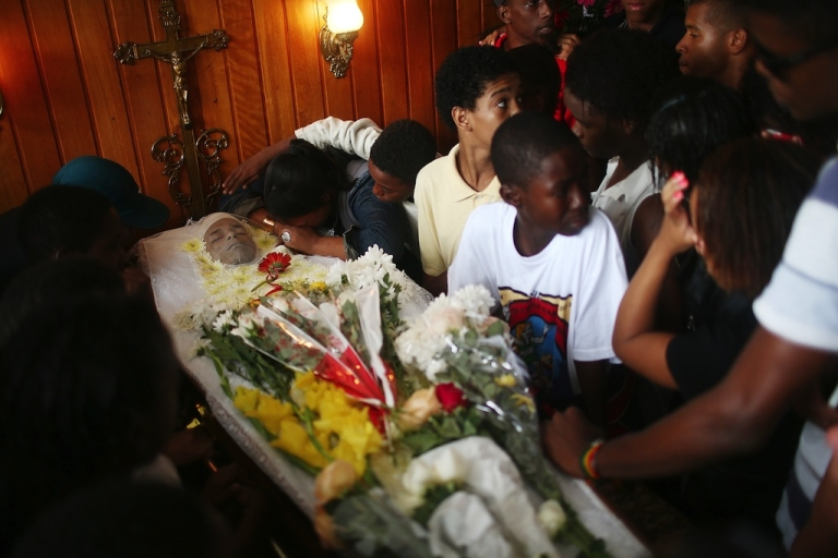 <p>Mourners gather over the body of dancer Douglas Rafael da Silva at his funeral, after he was shot and killed, on April 24, 2014 in Rio de Janeiro, Brazil. Da Silva's body was discovered in the pacified Pavao-Pavaozinho community, just blocks from Copacabana Beach, on April 22. Protests and shootings broke out as a result after protesters alleged he was killed by police in the pacified 'favela'.</p>