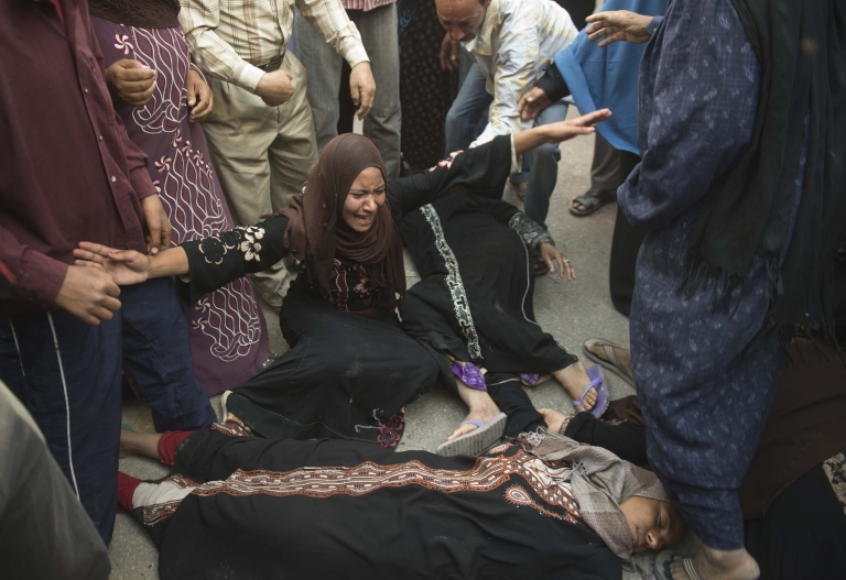 <p>Egyptian women faint as they react outside the courtroom in Minya after the sentences were announced.</p>