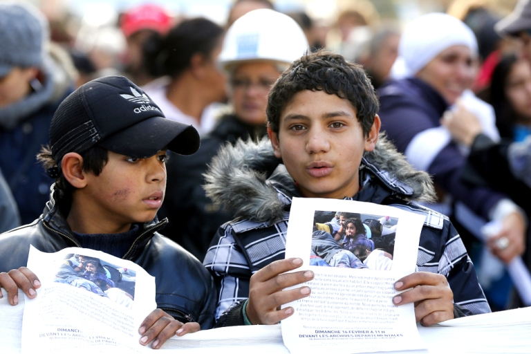 <p>Two children hold a picture of Melissa, an eight-year old Bulgarian Roma girl who perished in a fire that destroyed her camp in the Paris suburbs earlier in the week, during a white march commemorating her death, in Bobigny, near Paris, on February 16, 2014.</p>