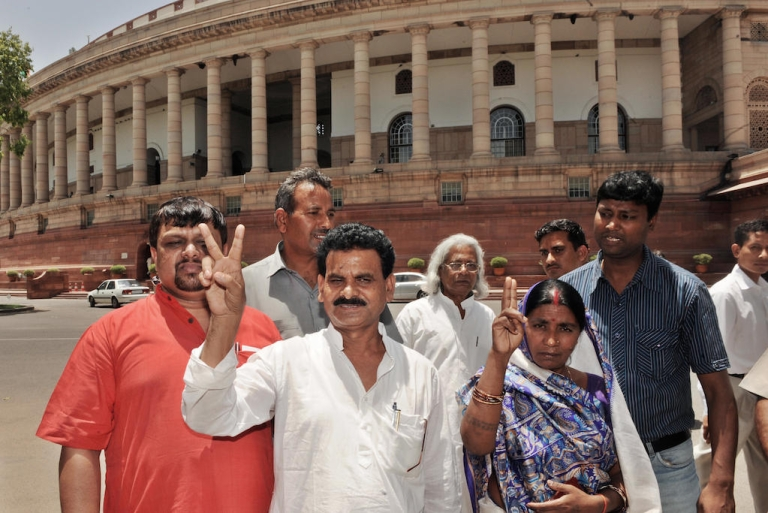 <p>Kameshwar Baitha and his wife show the victory sign at Parliament House in New Delhi in June 2009. One of the most feared Maoist commanders he contested India's 2009 general election from inside a jail, with a 500,000 Indian Rupee reward on his head and dozens of criminal cases pending. He is running for parliament once again in the election concluding in May 2014.</p>