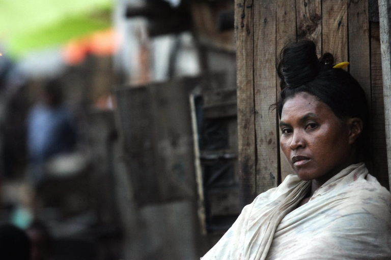<p>Antananarivo, MADAGASCAR:  A Malgachi woman stands outside her shack in the poor