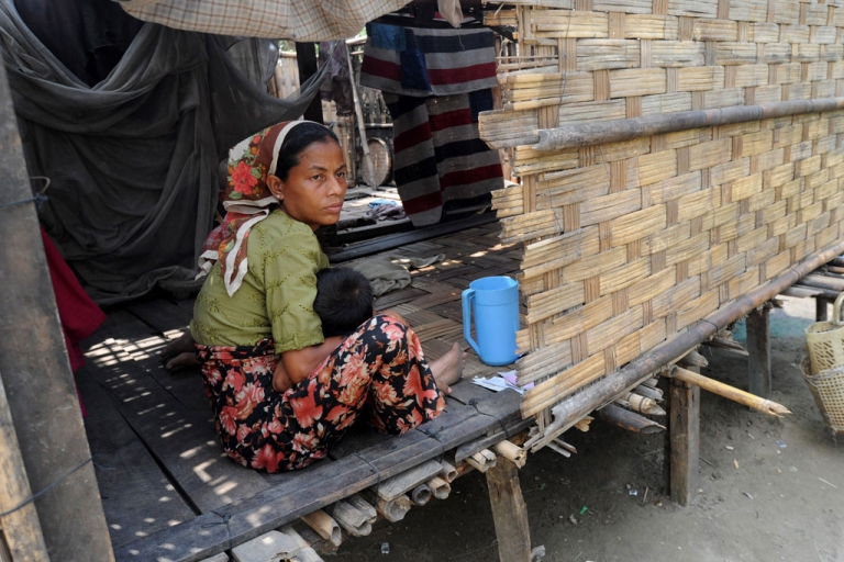 <p>A Muslim woman holds her baby in front of her home at Bumay village, outskirts of Sittwe in the western Myanmar state of Rakhine on March 31, 2014</p>