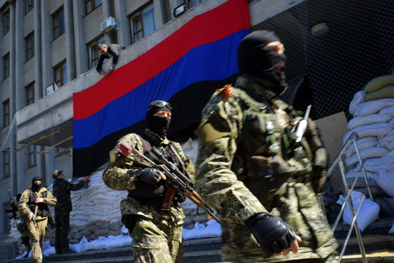 <p>A pro-Russian activist hangs a flag of the so-called 'People's Republic of Donetsk' on the regional administration building seized by separatists in the Ukrainian city of Slavyansk on April 21, 2014.</p>