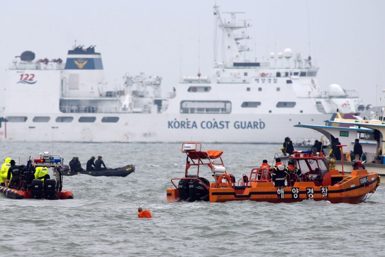 <p>South Korean coast guards and rescue workers are seen at the accident site of the capsized South Korean ferry Sewol in Jindo on April 22, 2014.</p>