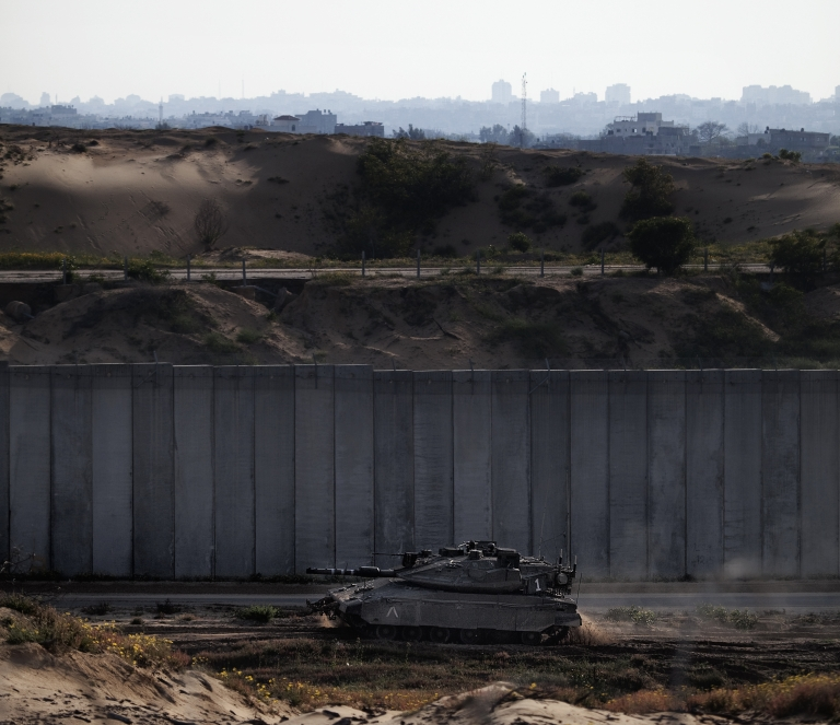 <p>An Israeli tank patrolling the concrete barrier dividing the coastal strip from Netiv Haasara in 2011.</p>