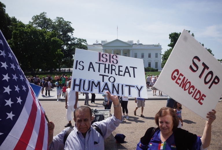 <p>Demonstrators at a rally supporting Kurdistan hold placards protesting against the Islamic State in front of the White House on August 16.</p>
