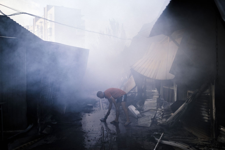 <p>A man collects water to fights a fire after the shelling of an open market in the town of Yasynuvata near the rebel stronghold of Donetsk on Aug. 12, 2014.</p>