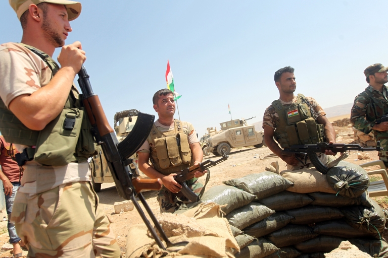 <p>Iraqi Kurdish Peshmerga fighters monitor the area from their front line position in Bashiqa, a town north-east of Mosul, on Aug. 16, 2014.</p>