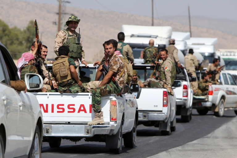 <p>Iraqi Kurdish peshmerga fighters drive trucks as they head to the Mosul dam on the Tigris river that they recaptured from Islamic State militants.</p>