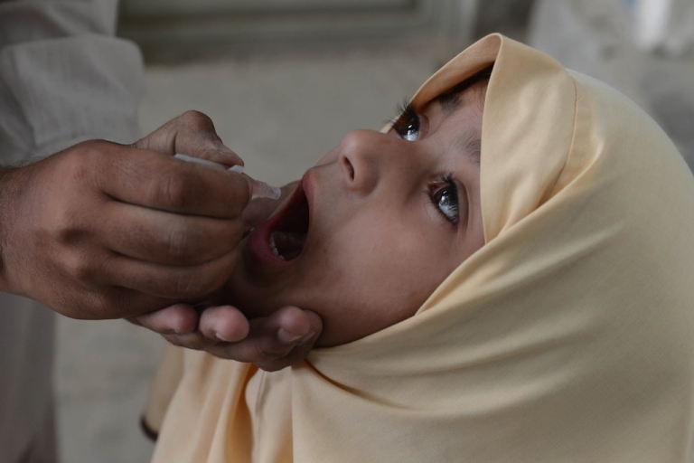 <p>A Pakistani health worker administers polio vaccine drops to a young girl in Quetta on May 12, 2014. Pakistan will set up mandatory immunization points at airports to help stop its polio outbreak spreading abroad.</p>