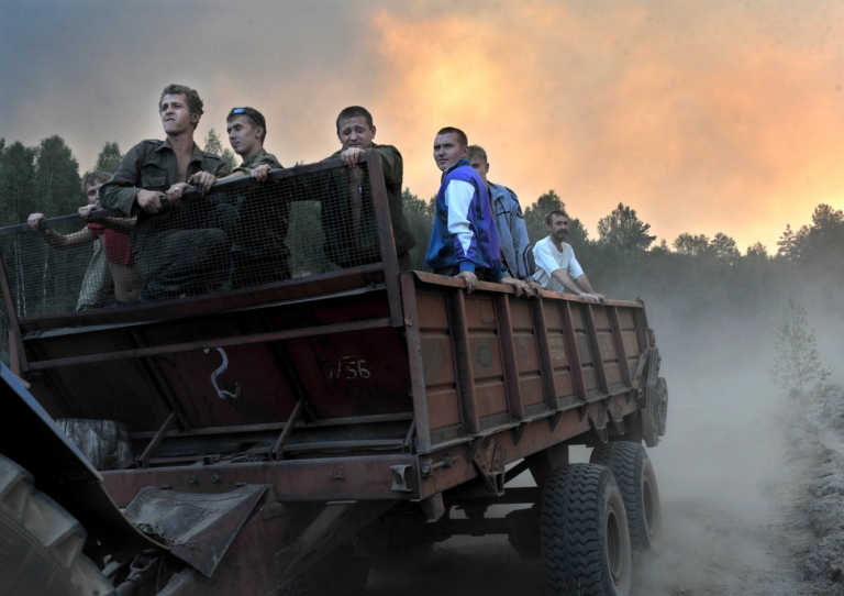 <p>Volunteer firefighters are driven to a wildfire near the village of Tokhushevo, in western Russia, on Aug. 11, 2010.</p>
