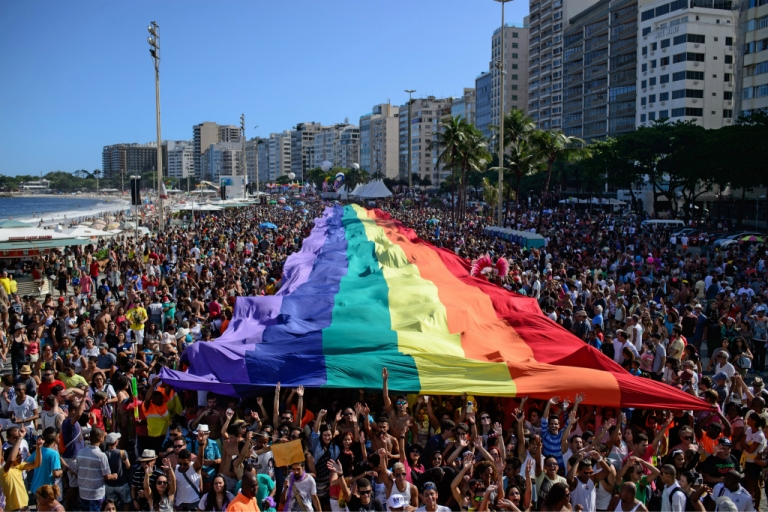 <p>Revellers march with a giant rainbow flag during the annual Gay Pride Parade at Copacabana beach in Rio de Janeiro, Brazil, on November 16, 2014.</p>