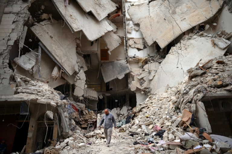 <p>A Syrian man walks amid destruction in the northern Syrian city of Aleppo on April 10, 2013.</p>