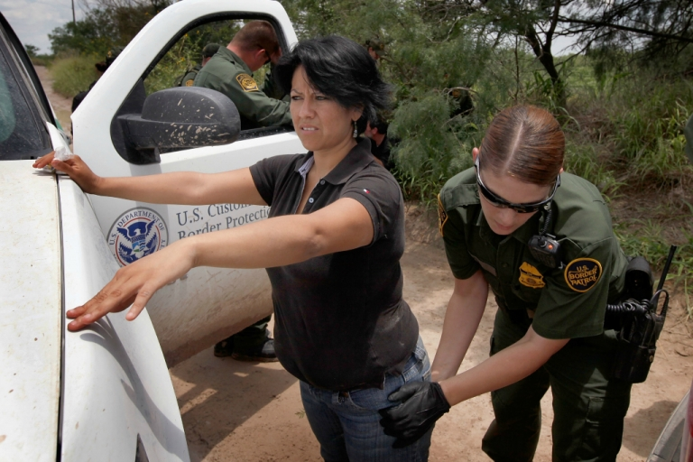 <p>A Border Patrol agent searches an undocumented immigrant apprehended near the Mexican border on May 27, 2010 near McAllen, Texas.</p>