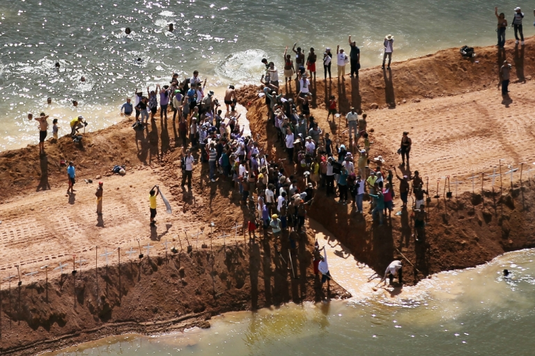 <p>Residents who are being displaced by the Belo Monte dam and supporters stand atop a temporary earthen dam at the Belo Monte construction site after removing a strip of earth to restore the flow of the Xingu River as a protest against the construction on June 15, 2012 near Altamira, Brazil. Belo Monte will be the world's third-largest hydroelectric project and will displace up to 20,000 people while diverting the Xingu River and flooding as much as 230 square miles of rainforest. The controversial project is one of around 60 hydroelectric projects Brazil has planned in the Amazon to generate electricity for its rapidly expanding economy.</p>