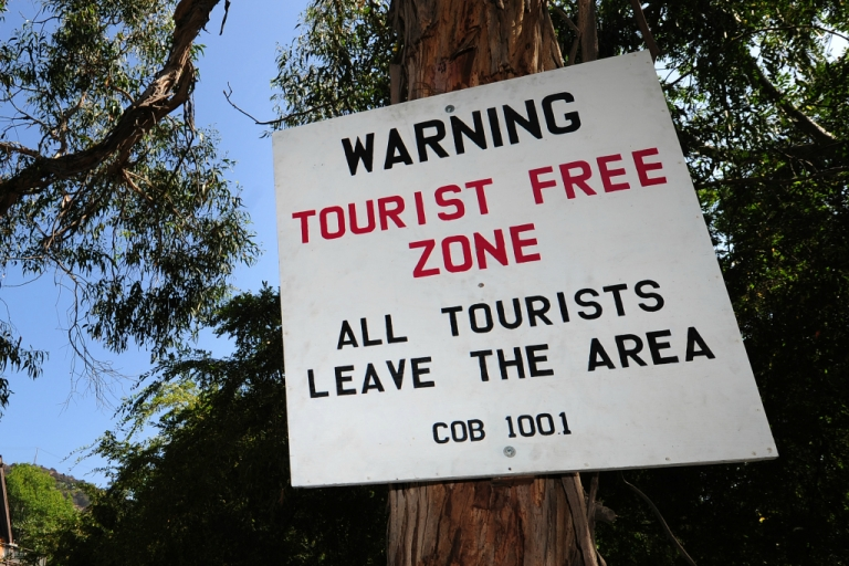 <p>A placard warning of a 'Tourist Free Zone' is posted along a road often used by tourists and locals near Hollywood.</p>