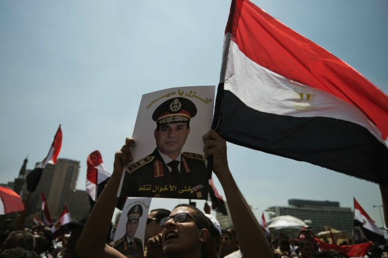 <p>An Egyptian man holds a portrait of military chief General Abdel Fattah al-Sisi that reads in Arabic