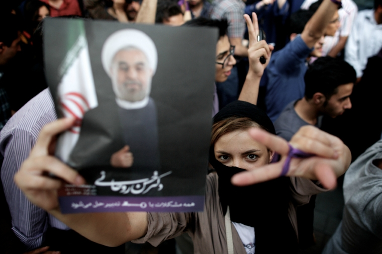 <p>An Iranian woman flashes the sign for victory as she holds a portrait of moderate presidential candidate Hassan Rouhani during celebrations for his win in the Islamic Republic's presidential elections.</p>