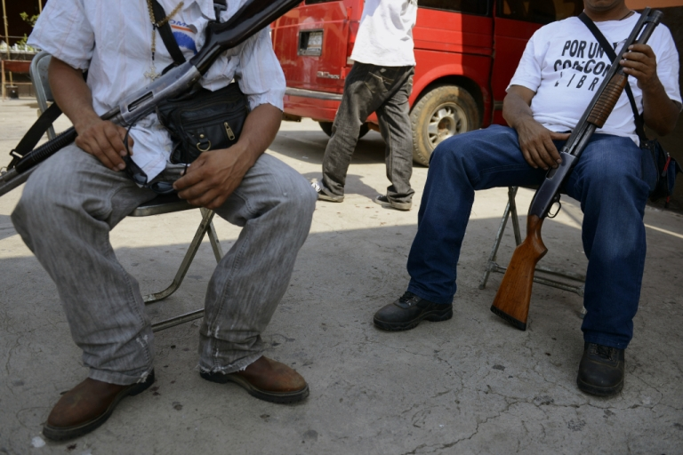 <p>Armed men - members of a vigilante group - keep watch in Coalcoman community, in Michoacan State, Mexico. Vigilante groups, calling themselves