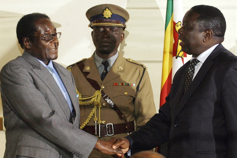 <p>Zimbabwean President Robert Mugabe (L) shakes hands with Movement for Democratic Change leader Morgan Tsvangirai on July 21, 2008 in Harare after the signing of a deal between Zimbabwe's opposition and ruling party, paving the way for full-scale talks.</p>