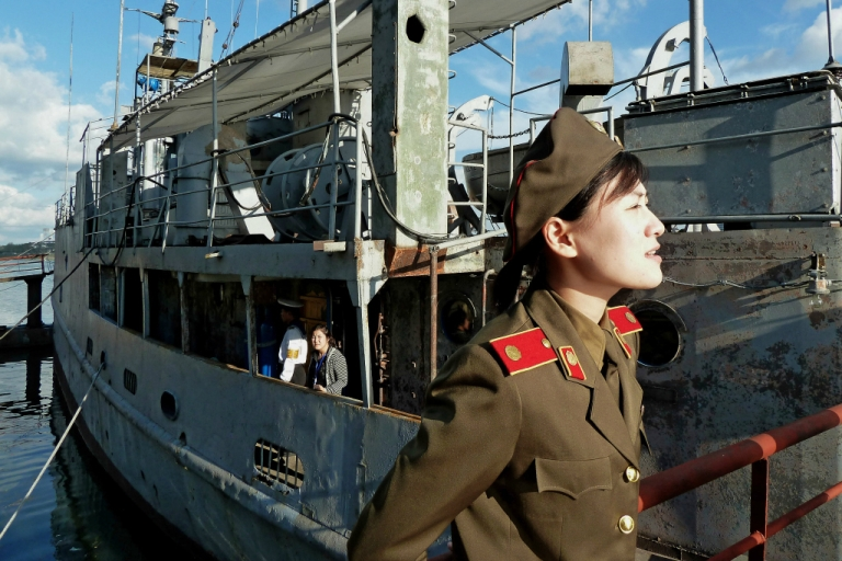 <p>This photo taken on September 22, 2010 shows a North Korean military female guide speaking to some visitors next to the captured USS Pueblo docked at a port in Pyongyang.</p>
