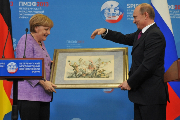 <p>Russia's President Vladimir Putin (R) presents Germany's Chancellor Angela Merkel with an old lithograph dedicated to the signing of a Russian-German trade agreement in 1894 at a press conference during an international economic forum in St. Petersburg, on June 21, 2013.</p>