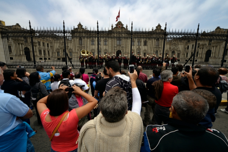 <p>Tourists listen and take pictures of the military band playing in the front patio of the Presidential Palace in Lima on October 31, 2013.</p>
