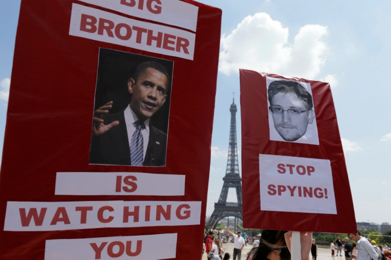 <p>Protesters hold up posters with pictures of US President Barack Obama and Edward Snowden, the former technical contractor of the US Central Intelligence Agency, during a demonstration in support of Snowden at the Place du Trocadero in front of the Eiffel tower in Paris on July 7, 2013.</p>