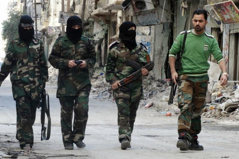 <p>Masked female rebel fighters walk alongside their trainer.</p>