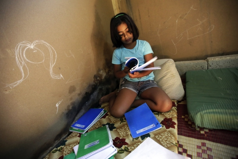 <p>Syrian refugee girl Mashaael, 7, looks at an old exercise book as she waits inside her makeshift house before heading to school on September 26, 2013 in the northern Lebanese city of Tripoli. UN children agency UNICEF said 257,000 Syrian children were seeking education in Lebanon in 2013, a number that could rise up to 400,000 next year. Mashaael was not able to register at school as she didn't meet the Lebanese public school system's standards.</p>