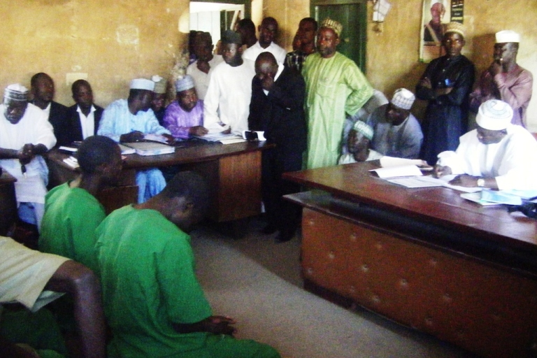 <p>A picture taken on January 22, 2014 shows two suspected homosexuals in green prison uniforms (L) sitting before Judge El-Yakubu Aliyu during court proceedings at Unguwar Jaki Upper Sharia Court in the northern Nigerian city of Bauchi. Two Islamic courts in northern Nigeria have been forced to suspend the trials of 10 men accused of homosexuality because of fears of mob violence, judges and officials have said on January 29. An angry crowd last week pelted stones at seven men suspected of breaking Islamic law banning homosexuality after their hearing was adjourned at the Unguwar Jaki Upper Sharia Court in Bauchi.</p>