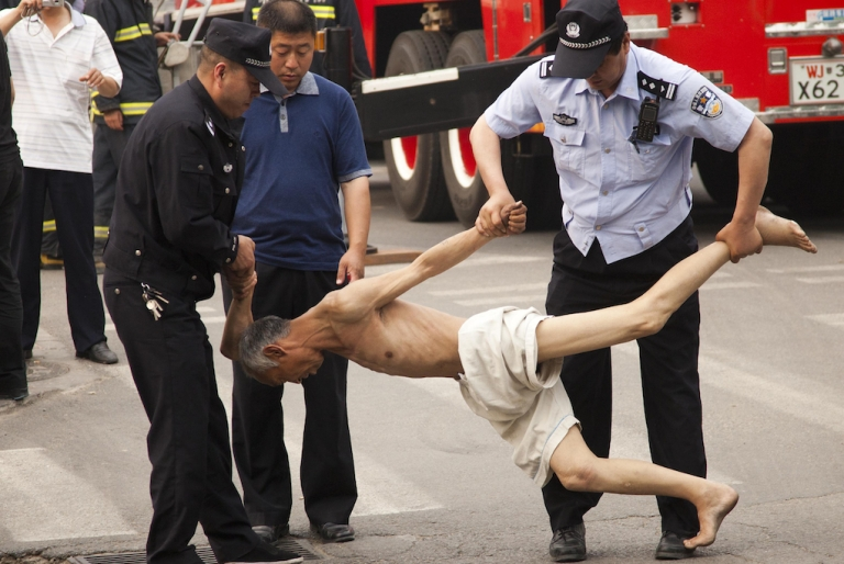 <p>Chinese police remove an elderly man who climbed up an advertising billboard to kill himself by jumping to the ground, in Beijing on May 17, 2011. The suicide rate among the elderly living in China's urban areas has become alarmingly high.</p>