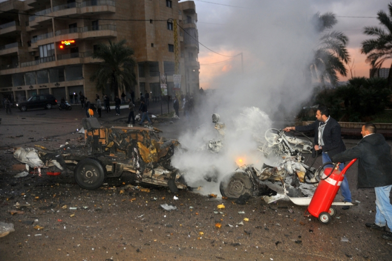 <p>Lebanese extinguish a minibus in fire at the site of an explosion on February 3, 2014 in Choueifat, south of the capital Beirut.</p>