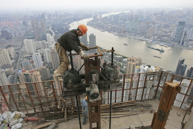 <p>A man works on the construction site of the Shanghai World Financial Center in 2006. China's quest for natural resources is enormous, but not as big as many claim.</p>